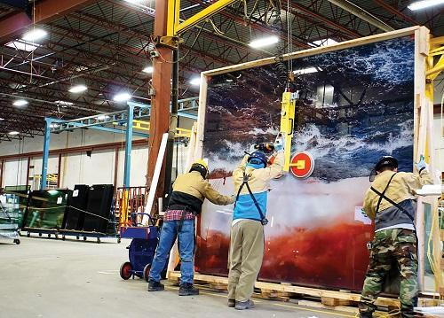 Fabrication personnel at the Vitrum plan use a crane to move a large piece of specialty glass.
