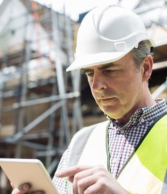 man on jobsite is reviewing information on phone